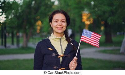 Slow motion portrait of proud American citizen smiling woman...
