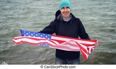 Slow motion portrait of proud American man holding US flag celebrating Independence day near the sea looking at camera and smiling. Patriotism and young people concept.