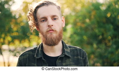 Slow motion portrait of serious bearded young man in...