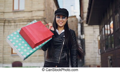 Slow motion portrait of smiling Asian woman shopaholic walking in the street with paper bags, turning and looking at camera enjoying purchases and city.