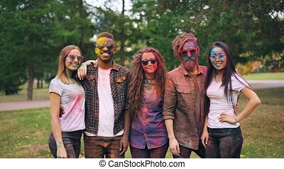 Slow motion portrait of smiling fiends girls and guys with colored faces and clothing standing outdoors and looking at camera at party. Holi festival and youth concept.