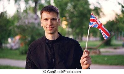 Slow motion portrait of smiling young man proud citizen...