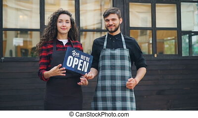 Slow motion portrait of smiling young people business partners holding sorry we are closed sign then turning it to another side with yes we are open sign.