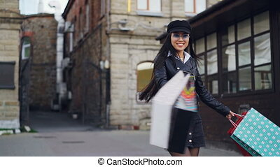 Slow motion portrait of young Asian lady in trendy clothing...