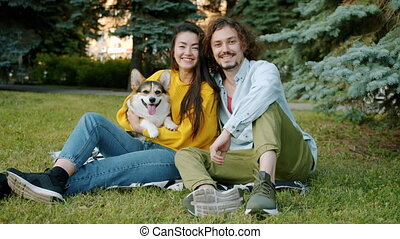 Slow motion portrait of young couple and corgi dog smiling relaxing in park