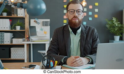 Slow motion portrait of young serious guy in casual clothing looking at camera at desk in modern office. People, career and modern technology concept.
