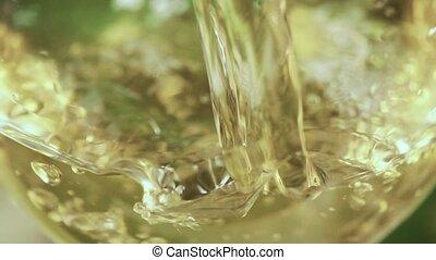 Slow motion pour a drink into a glass close-up
