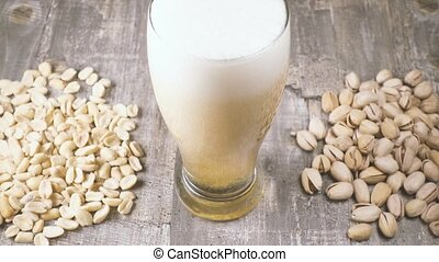 Slow motion pour beer into a glass and salted nuts on the table top view
