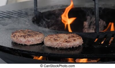 Slow motion: process of cooking two fresh meat cutlets for burgers on brazier with hot flame at summer local food market - close up view. Outdoor cooking, gastronomy, cookery, street food concept