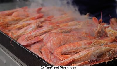 Slow motion: process of cooking fresh red langoustine on grill at summer local food market - close up. Outdoor cooking, barbecue, gastronomy, seafood, cookery, street food concept