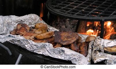 Slow motion: process of cooking fresh meat steaks and potatoes in foil on brazier with hot flame at summer local food market - close up view. Outdoor cooking, gastronomy, cookery, street food concept