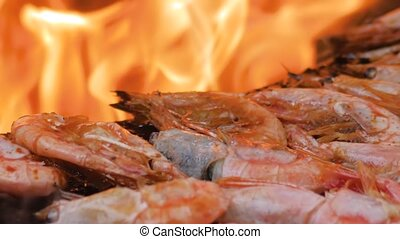 Slow motion: process of grilling fresh red king prawns on brazier with hot flame at summer local food market - close up macro view. Outdoor cooking, gastronomy, seafood, barbecue, street food concept