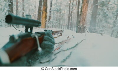 Slow Motion Re-enactor Dressed As World War II German Wehrmacht Infantry Soldier Sniper Shooting from Rifle With Optics in Winter Snowy Forest. Reload cartridge.