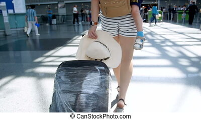 Slow motion rear view footage of young woman with little boy and big suitcase walking in airport terminal