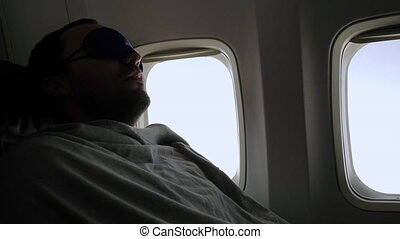Slow motion. Rest and comfortable flight in the plane. Man in a mask for sleeping. Professional shot in 4K resolution. 040. You can use it e.g. in your commercial video, medical, business, presentation, broadcast