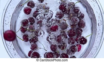 slow motion. ripe cherry falls into the water