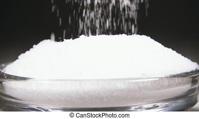 Slow motion salt mix with a spoon into a glass bowl close up