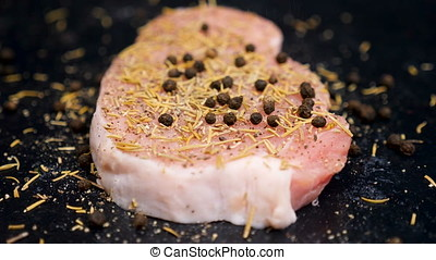 SLOW MOTION. Salt, pepper and spices falling on a piece of raw meat