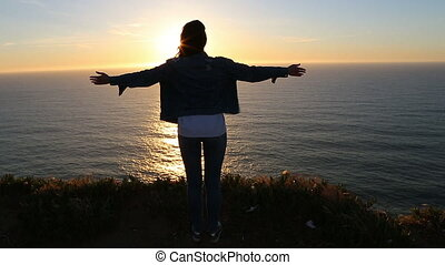 Slow Motion Scene of Successful Tourist Enjoying Scenic Sunset. Beautiful Young Woman Looking at Sunset Over the Ocean.