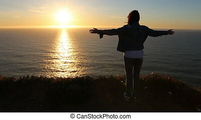 Slow Motion Scene of Successful Young Woman Looking at Sunset Over the Ocean. Relaxation Concept. HD 1080.
