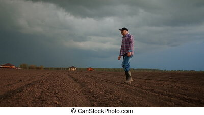 Slow-motion: senior male a tractor driver walks through a plowed field at sunset after work