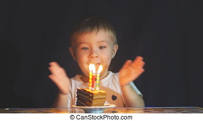 Slow motion sequence of little boy blowing out candles on birthday cake