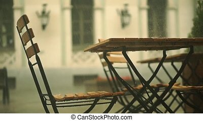 Slow motion shallow focus shot of street cafe in summer rain...