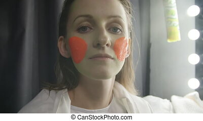 Video of girl applying paint on the model's face in studio