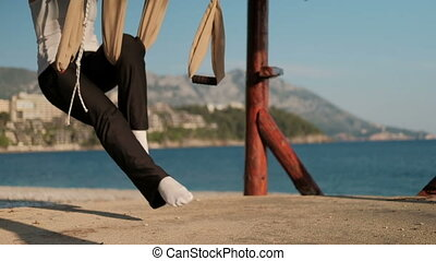 Slow-motion shooting swinging woman swing on shore of lake...