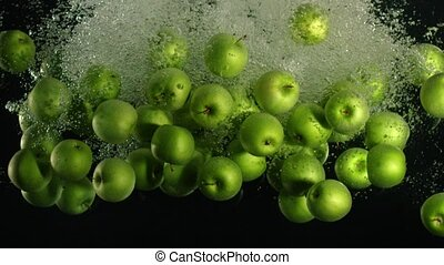 Slow motion shot: green apple falls and floats in water,...