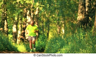 Slow motion shot of a defocused male athletic runner running in the park