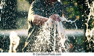Slow motion shot of a man catching fountain stream - Slow...