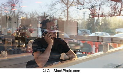Slow motion shot of a man sitting in cafe with a smartphone in hands