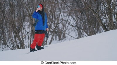 Slow motion shot of a snowboarder using a smartphone while...
