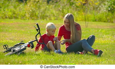 Slow motion shot of a young woman applying cut plaster on a knee of her little son and a bicycle laying next to them