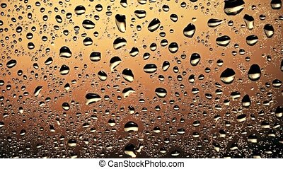 Slow motion shot of abstract water drops and streams moving on the glass, warm colors