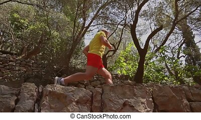 Slow motion shot of an athletic man running in Mediterranean scenery