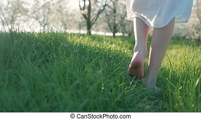 Slow motion shot of bare feet of young girl walking and running on green grass