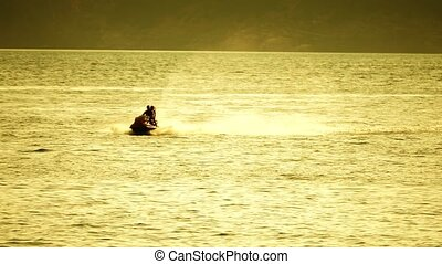 Slow motion shot of couple riding jet ski at sea in the...