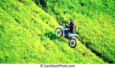 Slow motion shot of cross motorcycle moving uphill on the grass hill