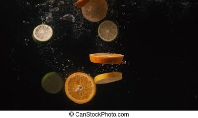 Slow Motion Shot of Falling slices of citrus into Water at ...