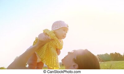 Slow motion shot of happy mother holding her cute baby girl at sunset