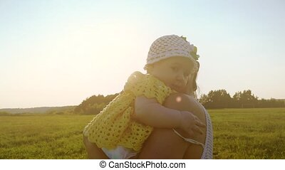 Slow motion shot of happy mother hugging her little baby girl at sunset