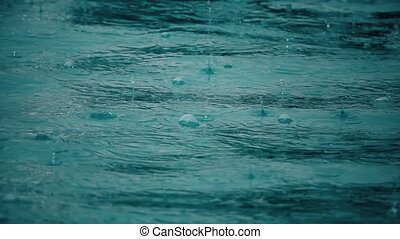 Slow motion shot of rain drops and bubbles on sea surface -...