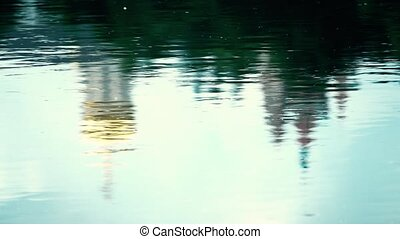 Slow motion shot of river ripple reflecting catholic...