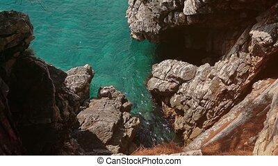 Slow motion shot of sea ripple near rocks on a sunny day -...