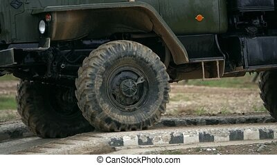 Slow motion shot of spinning wheels of a military truck