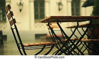 Slow motion shot of street cafe wooden tables and man with umbrella in the rain