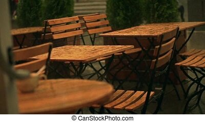 Slow motion shot of street cafe wooden tables in summer rain...