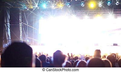 slow motion shot of the crowd looking towards the stage at a dance music festival. the crowd is in shadow